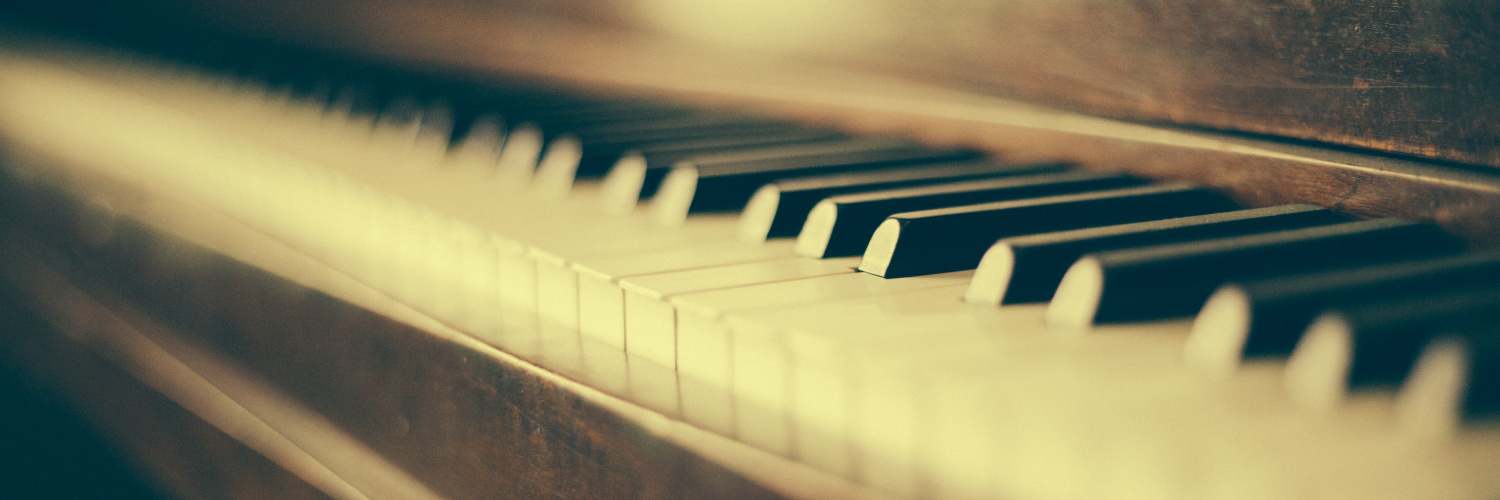 A photograph of the keyboard of an upright piano instrument