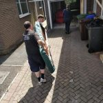 Two Bradway Premier Removals workers carefully carrying a dining table (Sheffield)